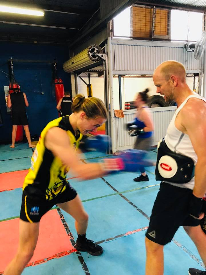 Young boxer throws rapid punches to mid of trainer